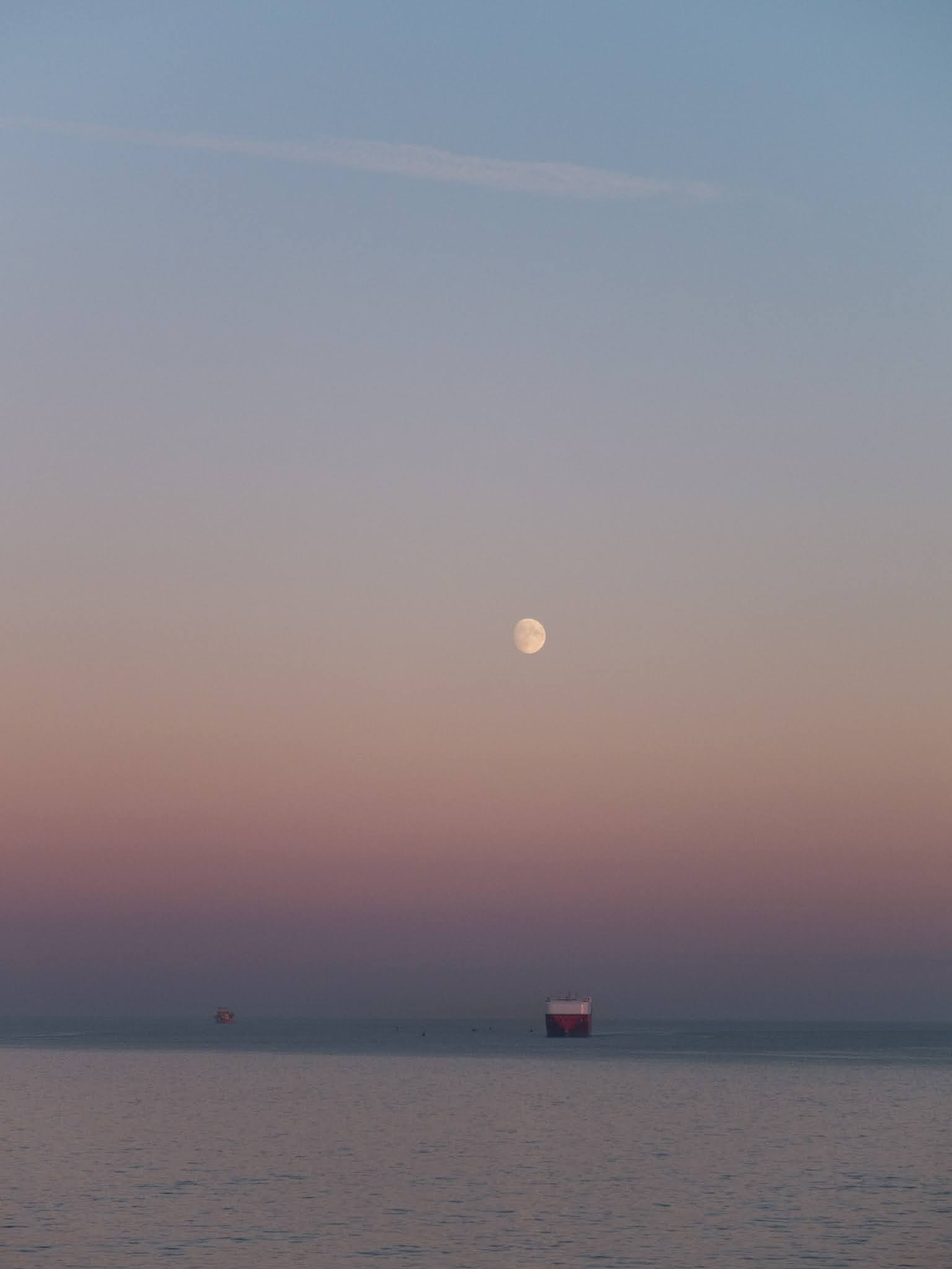 Moon rising over the North Atlantic Ocean with ships in the background.