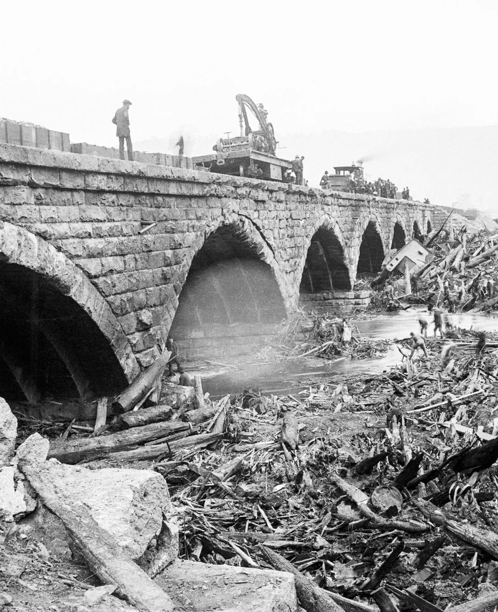 Volunteers search for bodies in the debris piled up against the stone bridge.