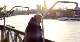 Woman standing wrapped in a blanket looking out over the Thames
