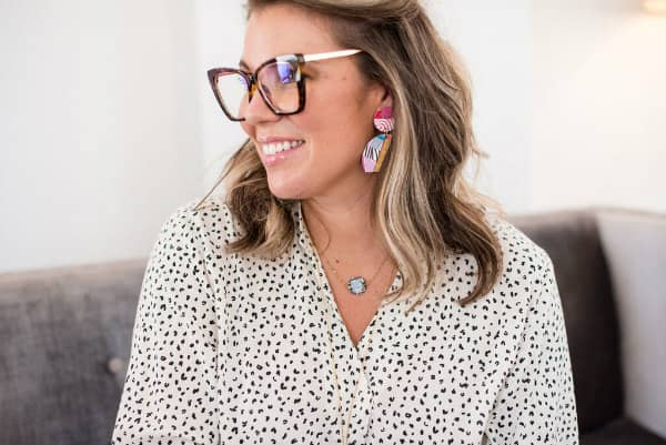 woman modeling bright earrings, necklace and glasses
