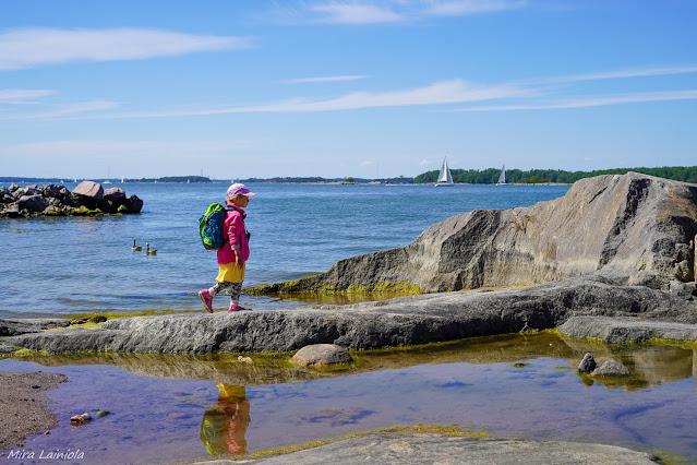 Lapsi kävelee rantakalliolla meren ääressä