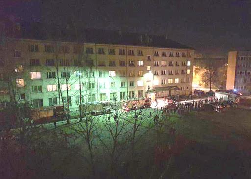 Pie ēkas stāv VUGD ekipāžas un evakuēti cilvēki