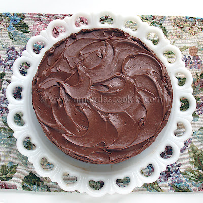 An overhead photo of a Nigella\'s old fashioned chocolate cake resting on a white cake stand.