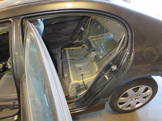 Interior of car with seats and interior panels removed so new floor can be installed.
