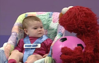 Elmo goes to a baby and puts the ball in the baby's lap. The ball drops to the ground and they watch it bounce. Elmo's World Balls Kids and Baby
