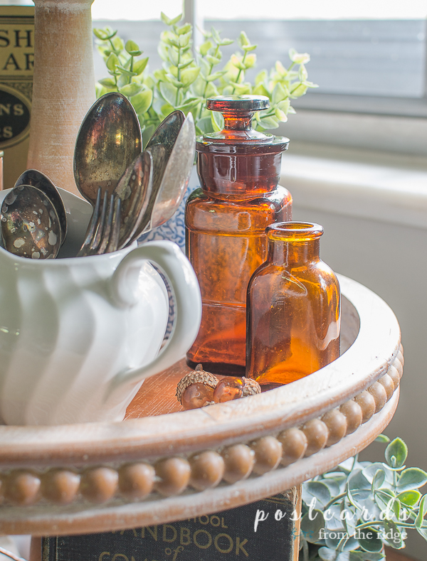 old silver, amber bottles, and books on wood tiered tray