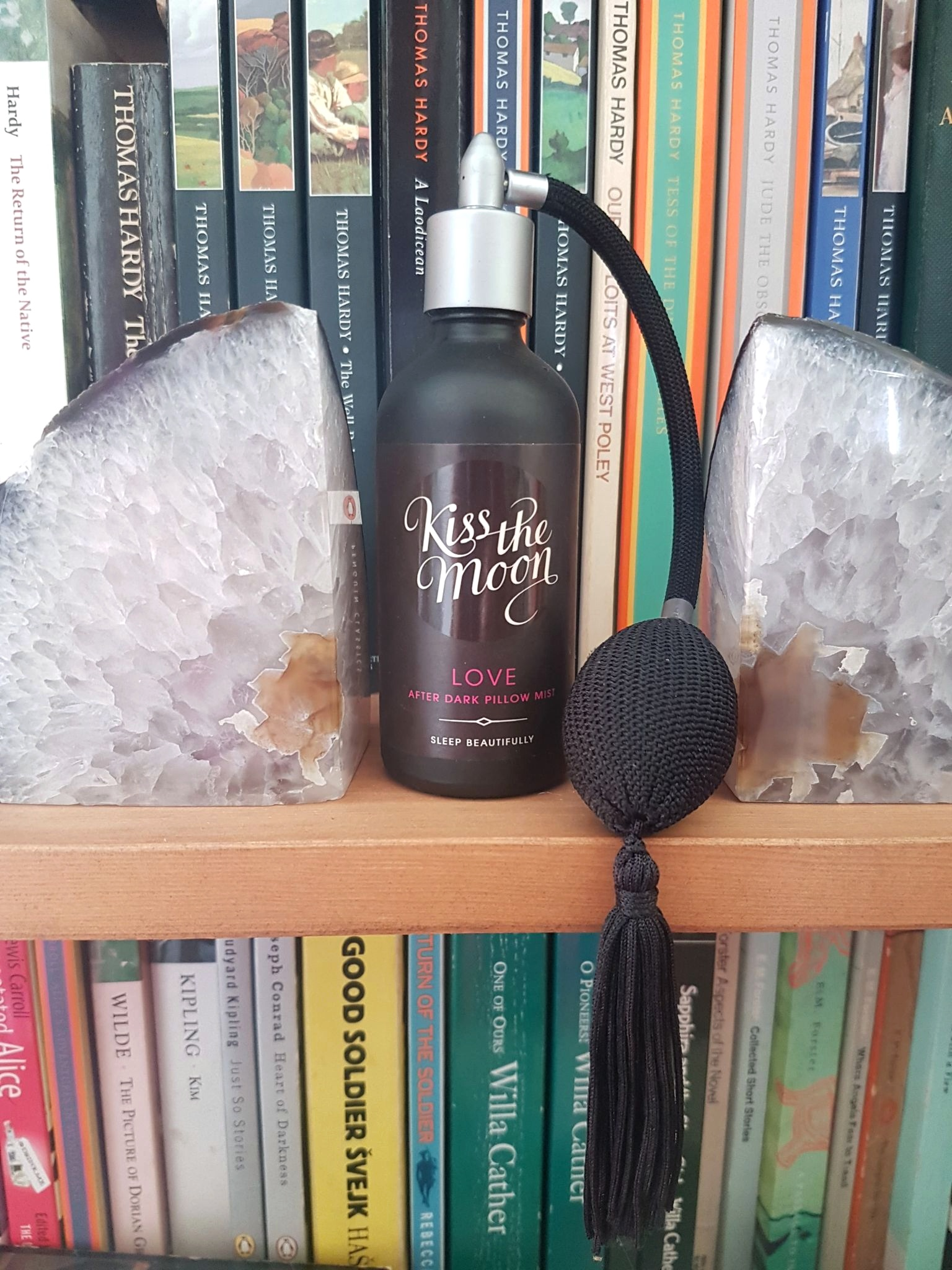 Kiss the Moon Love After Dark Pillow Mist on a bookshelf with two crystal geode bookends