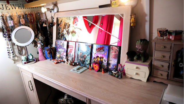 A cluttered dressing table with DVDs, toys, jewellery stands and boxes arranged on it, somewhat haphazardly.