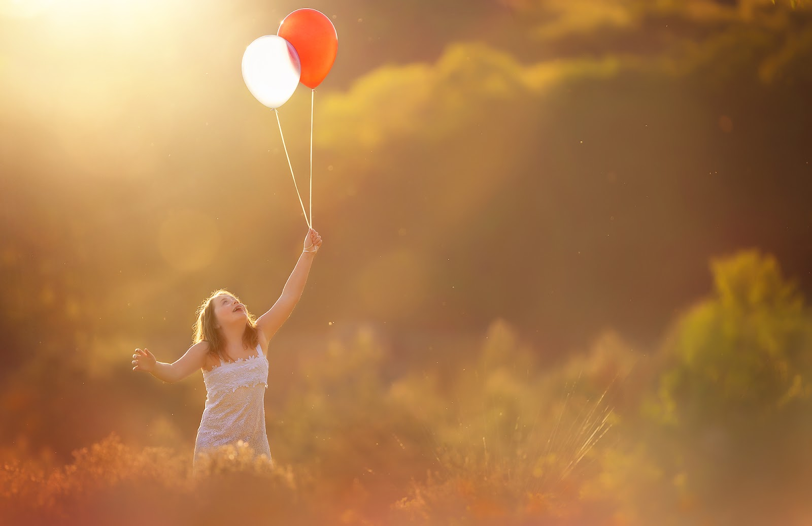 Canon color sunset portrait running with big red and white balloons through a field of gold by Willie Kers