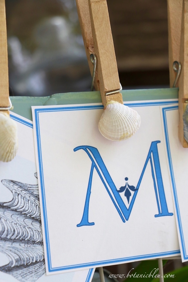 diy-shell-clothespin-holding-banner-letter