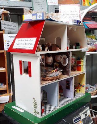 Child's wooden dolls' house filled with home-made furnishings.