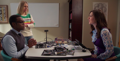 Chidi and Janet sit on opposite sides of a table, and Eleanor stands off to the side next to Chidi. On the table, there's a mess of computer parts and wires.