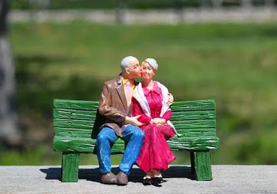 Homem idoso beija o rosto de sua esposa no banco da praça