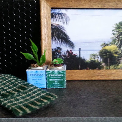 One-twelfth scale modern miniature scene of a kitchen bench with two Twinings tea tins with plants growing in them, a tea towel a framed picture of a New Zealand scene displayed.