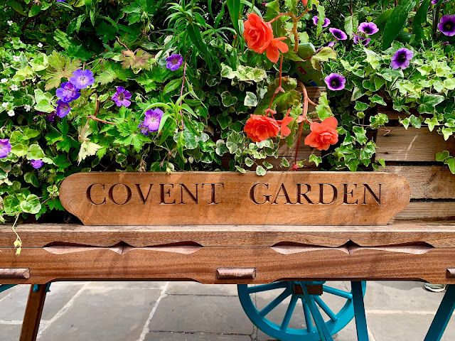 A flower cart with a sign saying covent Garden