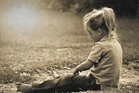 Kind sitzt draußen auf dem Boden