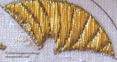 Close-up of completed section of underside couching showing gold metallic threads before burnishing