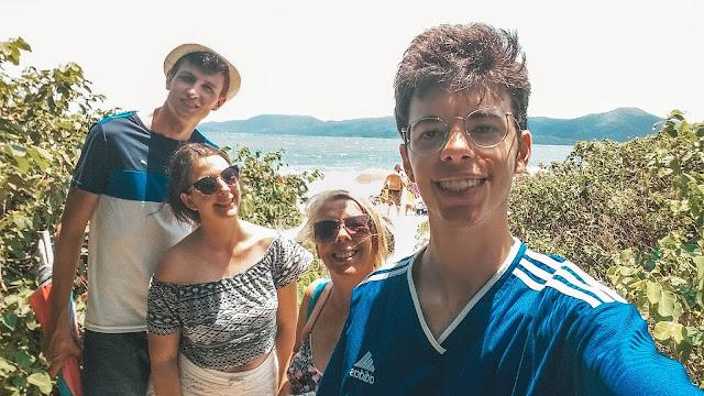 4 pessoas sorrindo na selfie, com mar no fundo