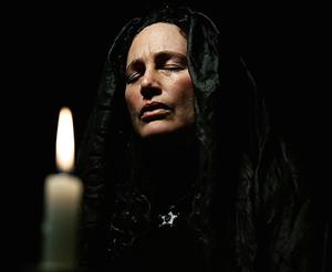 mujer rezando a la luz de una vela