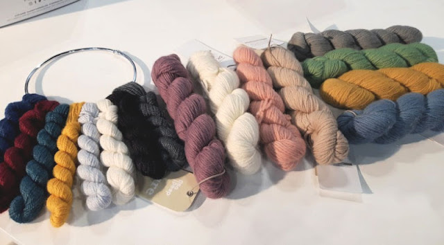 Image shows 8 mini skeins of yarn on a metal ring, and 8 larger skeins of yarn next to them
