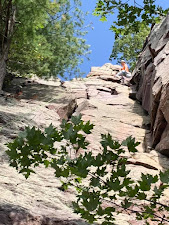 I am on a rope nearing the top of a rocky bluff. There are a few trees along the edges.