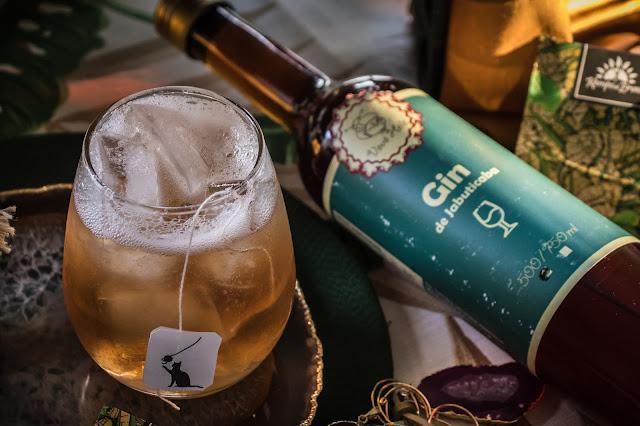 Copo com Gin tônica e garrafa de gin de jabuticaba ao lado