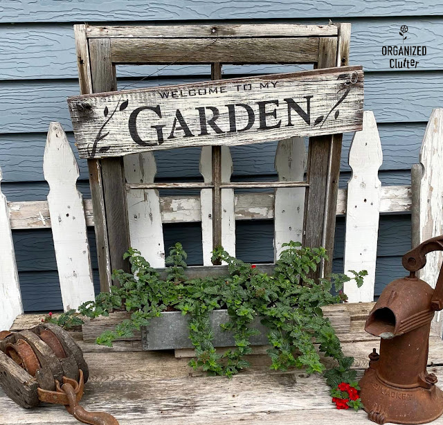 Photo of a weathered window frame and garden sign