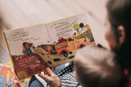 A person reading to a toddler