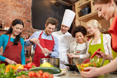 Image of a group of young people cooking under the direction of a chef.