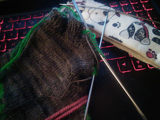 A double-knit fingerless glove on double pointed needles. Two fingers are complete and another finger is on the needles.  A sewn double-pointed needle case is just behind.