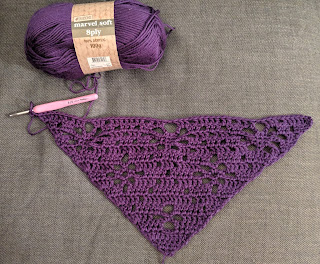"""Work in progress crochet triangle shawl in purple acrylic yarn, with the ball of yarn above with label """"Marvel soft 8 ply"""". The crochet hook attach at the top of the triangle of crochet."""