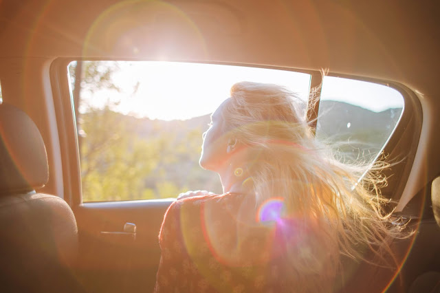 A blonde girl looking out the window while sitting backseat in a car.