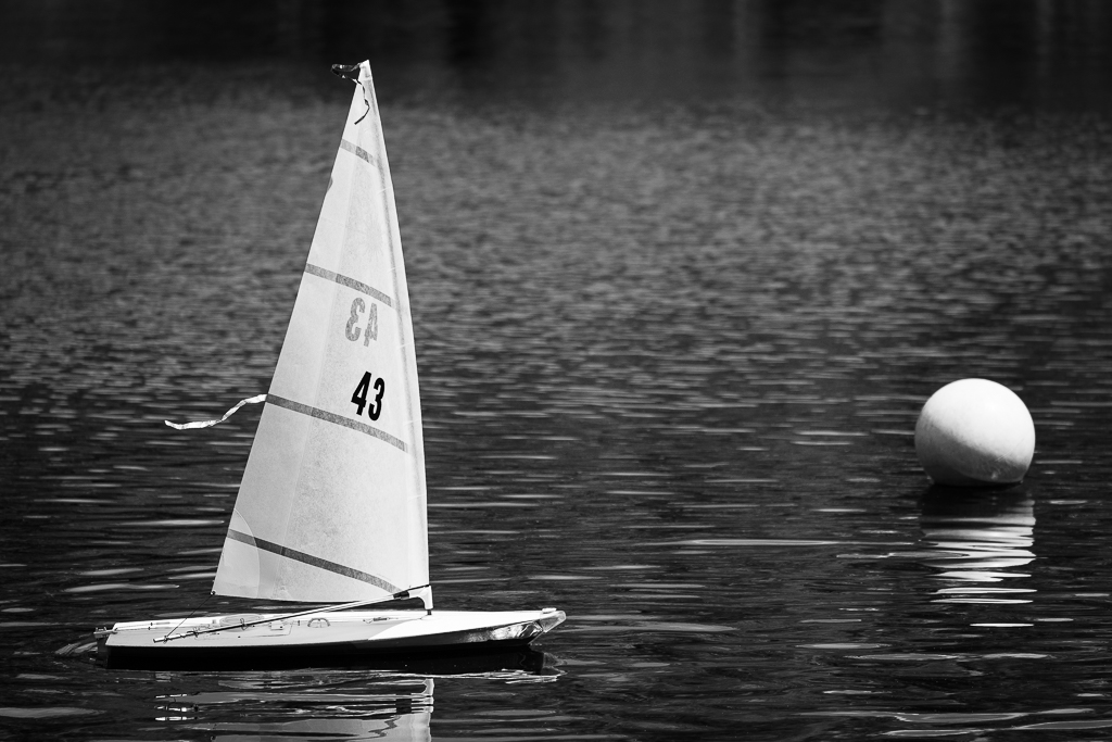 a black and white photograph of a radio controlled toy boat in central park