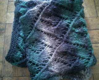 A folded lace scarf, knit with worsted-weight colour changing yarn  Colour changes from beige; grey; brown; black; and forest green.