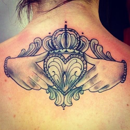 chica con tatuaje celta del claddagh en la espalda