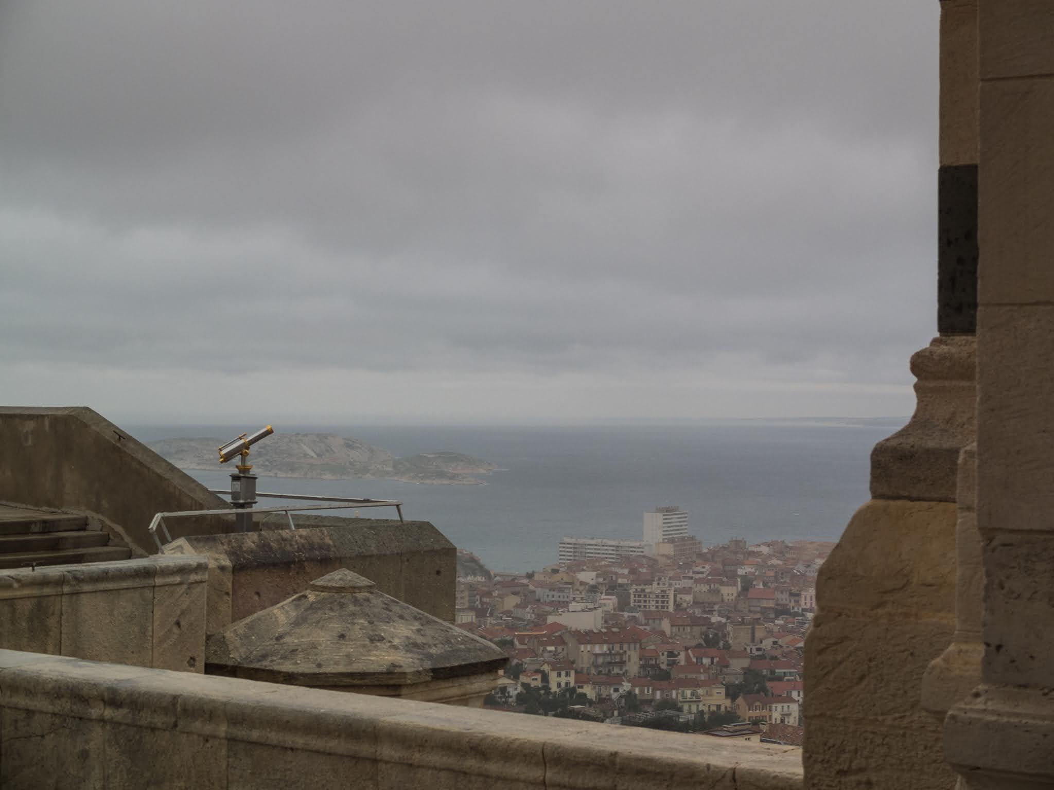 A brass telescope overlooking Marseille at the Basilica of Notre Dame de la Garde.