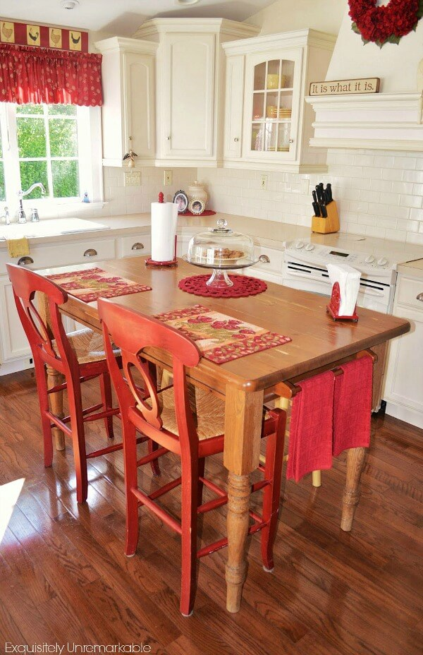 Farmhouse Kitchen Table Turned Island with red accents and wooden floor