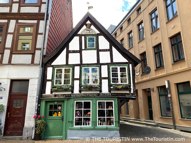 A small sized two-storey timbered house with a bright green entrance door and colourful windows and a wooden sculpture of a man in its gable.