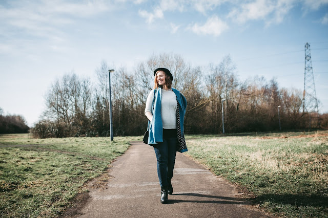 image shows a woman walking on a path through a country park on a sunny day and smiling off camera