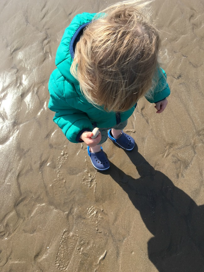 toddler holding pebble