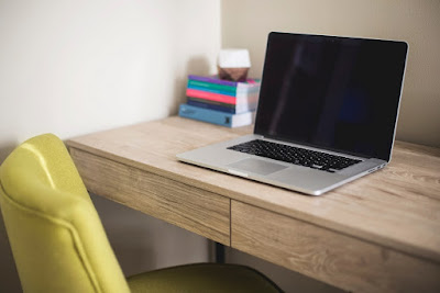Laptop open on a tidy desk with yellow chair