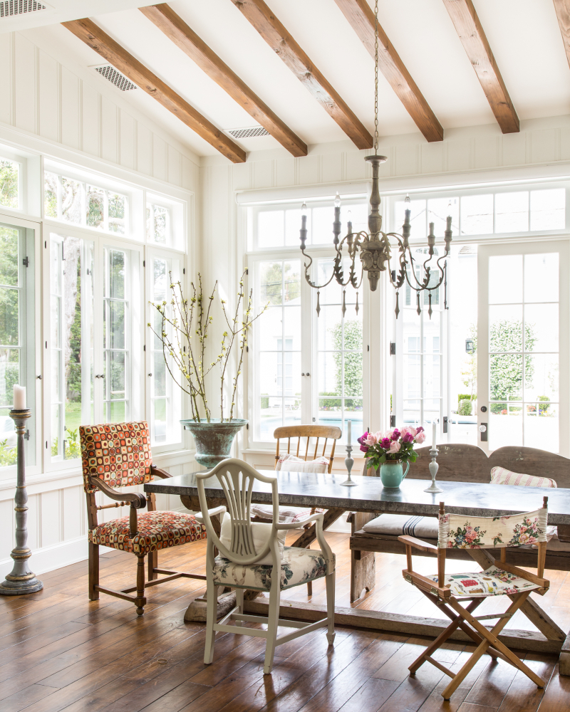 Eclectic farmhouse style dining room with mixmatched chairs and surrounded by windows with decor by Samantha O'Connor