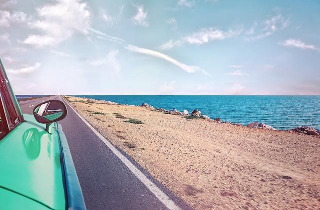 green 60s car driving along sandy beach highway