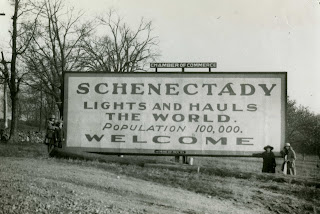 "Photo of bilboard nex to a road. Bilboard reads ""Schenectady Lights and Hauls the World. Population 100,000. Welcome"""