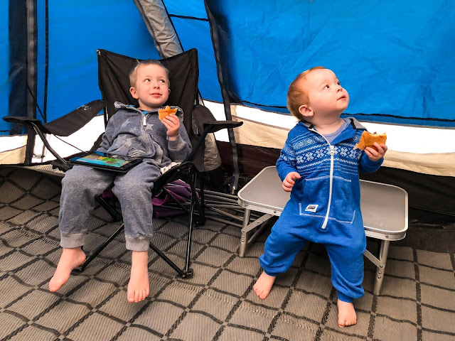 two young boys wearing onesies and eating pastries in a blue caravan awning