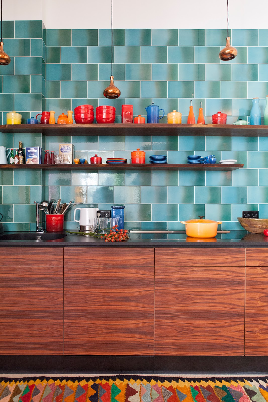 colorful kitchen in Berlin designer loft, wood cabinets, colorful pattern rug, 60s style