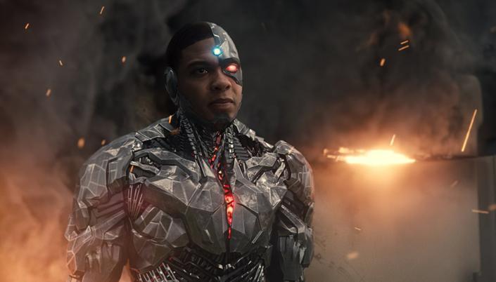 Imagem: o Ciborgue, interpretado por Ray Fisher, um jovem negro com a maior parte do seu corpo composto por um corpo robótico, feito de armadura metálica, o seu olho direito substituído por um olho biônico vermelho e uma luz azul pisca em sua testa, ao fundo os destroços de uma explosão soltam fagulhas.