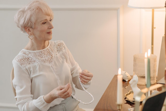 Beautiful elderly woman trying out a pearl necklace in front of her vanity area.