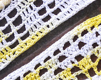 Close-up photo of the two border patterns, juxtaposed diagonally. The top has a filet pattern of two open squares followed by  a closed square. This is repeated row on row to give an effect of 1-square wide columns and spaces between them that are 2 squares wide, with a solid filet border of tr around the outside edge.  The bottom filet crochet  border has a chequerboard arrangement of open and solid squares. The outside edge is a round of open filet squares and a round of solid dc.