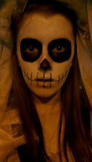 A close up of my bride of the dead makeup, featuring a skull-like look, with dark black eyes, white face and skeleton mouth, pulling a spooky, eyes-wide expression.